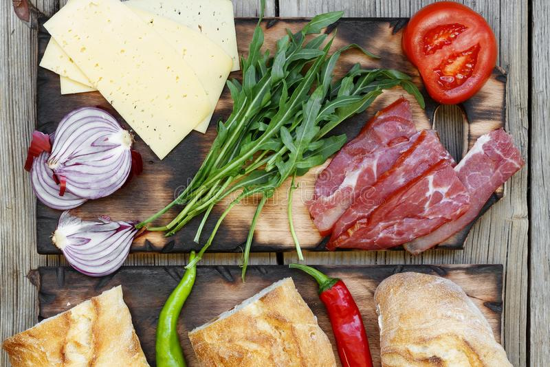 Sandwiches. Ingredients for tasty sandwiches with ham and fresh vegetables stock image