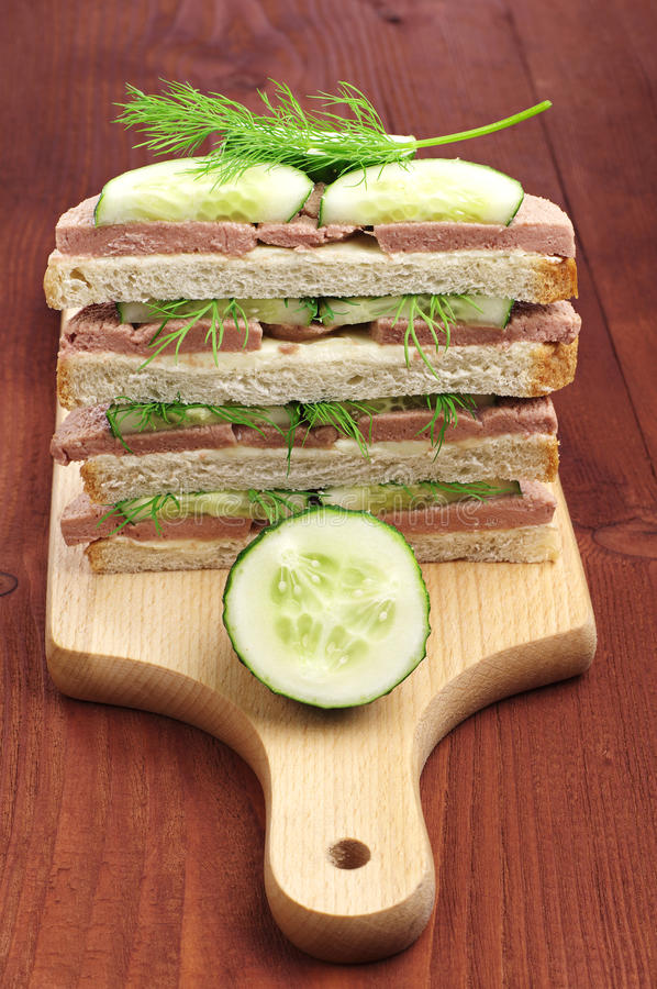Sandwiches with liver sausage and cucumber on cutting board
