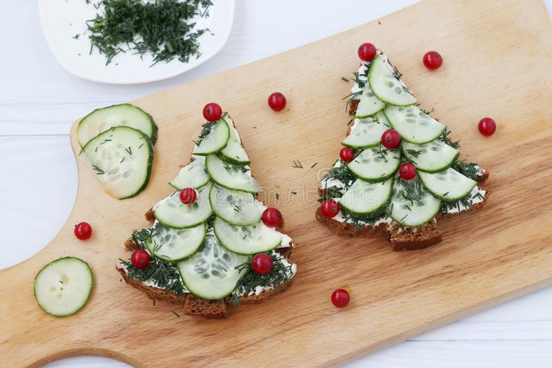 Sandwiches made of black bread, cheese and cucumber in the form of a Christmas tree decorated with berries, are placed on a wooden royalty free stock images