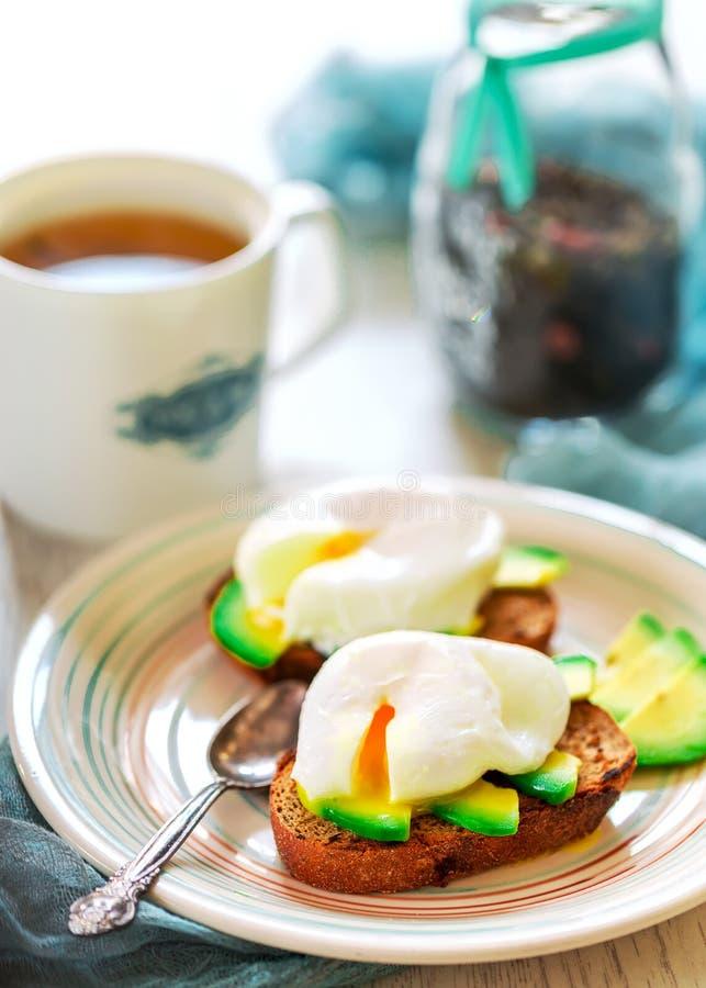 Sandwiches met avocado en gestroopte eieren Kop thee in de rug stock afbeeldingen