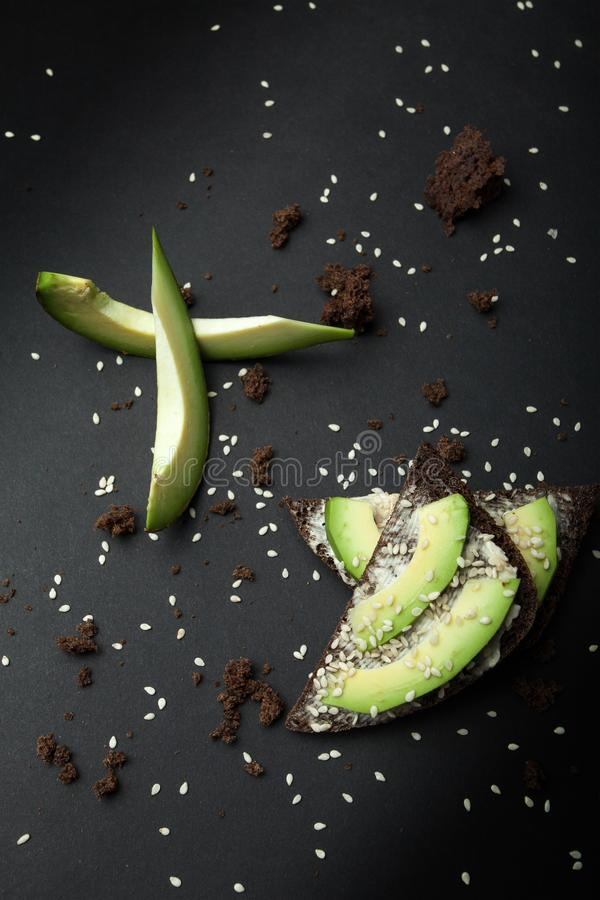 Sandwiches met avocado en kaas op zwart roggebrood met sesamzaden op een donkere achtergrond gezond ontbijt vegetarisch voedsel royalty-vrije stock afbeeldingen
