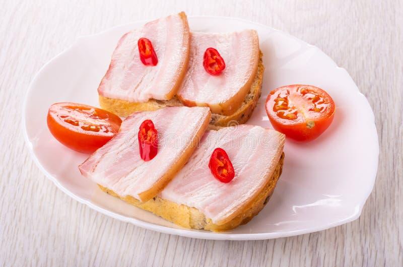 Sandwiches met borststuk, Spaanse peperpeper, stukken van tomaat in schotel op lijst royalty-vrije stock foto