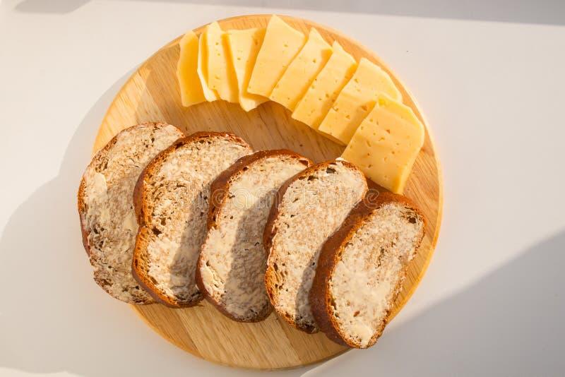 Sandwiches met boter en gesneden kaas op een ronde houten raad royalty-vrije stock fotografie