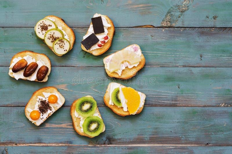 Sandwiches met een verscheidenheid van het vullen op een groene houten rustieke achtergrond Mening van hierboven Zoete sandwiches stock afbeelding