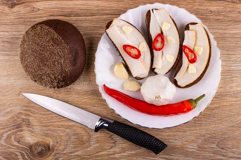 Sandwiches met gezouten reuzel, knoflook, Spaanse peperpeper in plaat, brood, mes op lijst Hoogste mening royalty-vrije stock afbeeldingen