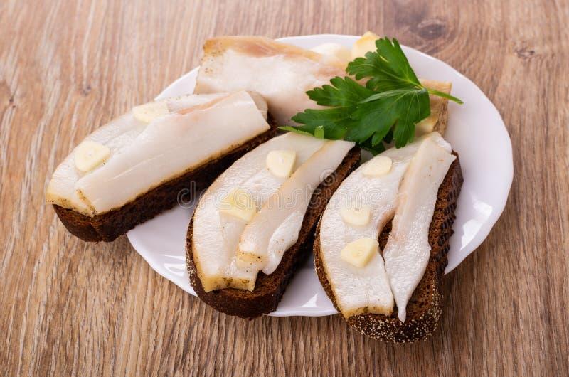 Sandwiches met gezouten varkensvleesreuzel, knoflook, peterselie in plaat op lijst stock foto