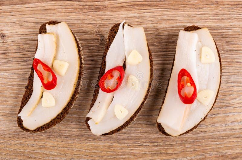Sandwiches met gezouten varkensvleesreuzel, knoflook, Spaanse peperpeper op lijst Hoogste mening stock afbeeldingen