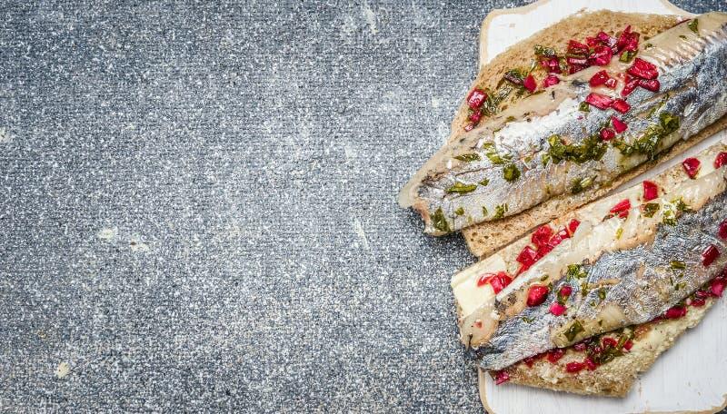 Sandwiches met ingelegde haringenvissen op grijze achtergrond, hoogste mening royalty-vrije stock foto