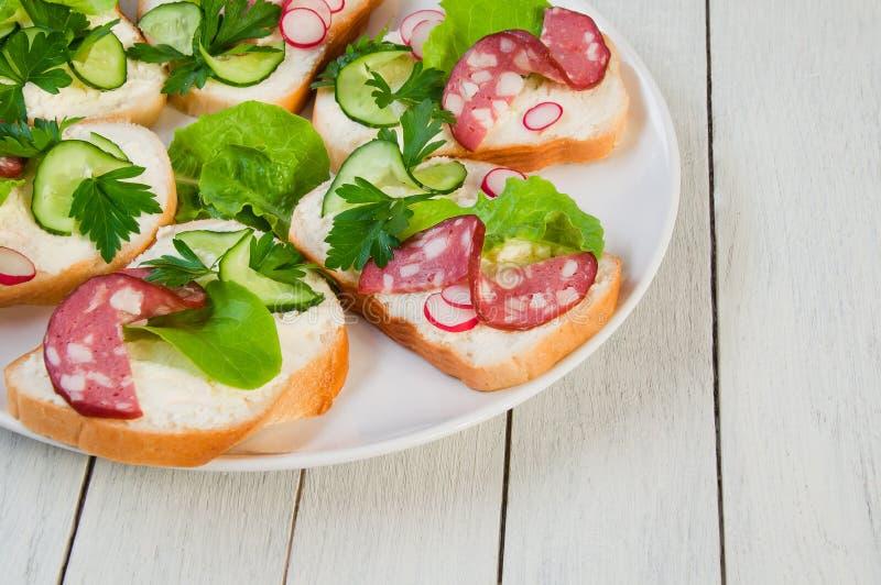 Sandwiches met worst en greens op een plaat op wit houten Ta royalty-vrije stock fotografie
