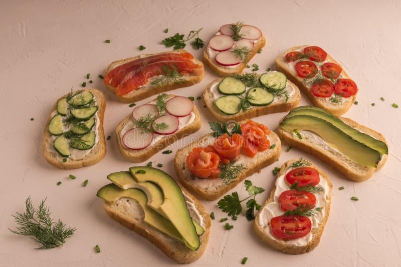 Sandwiches met zalm, komkommer, tomaten, avocado's en greens, gesneden groente stock fotografie