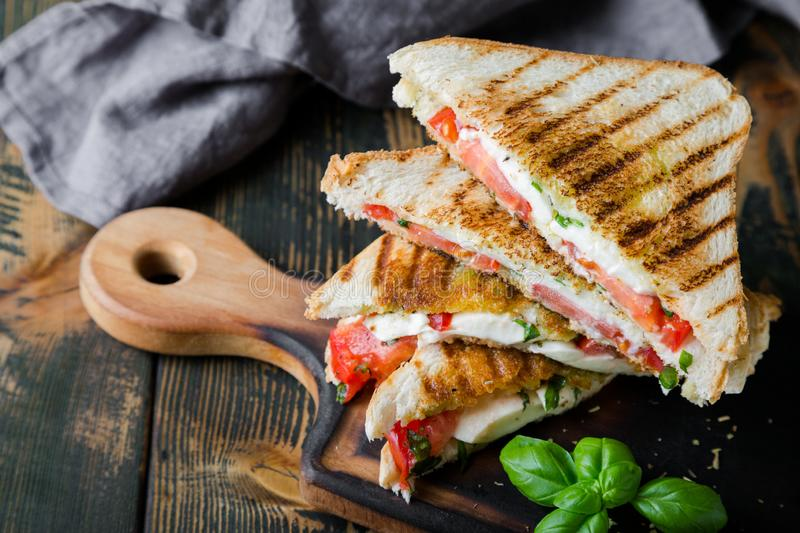 Sandwiches with mozzarella, basil and tomatoes. Italian sandwich. Grilled Italian sausage sandwich with mozzarella and tomatoes royalty free stock image