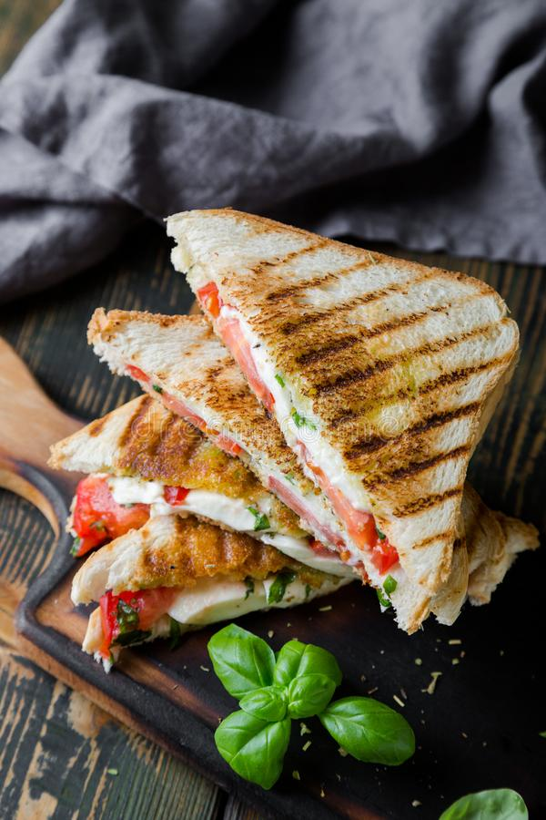 Sandwiches with mozzarella, basil and tomatoes. Italian sandwich. Grilled Italian sausage sandwich with mozzarella and tomatoes royalty free stock images