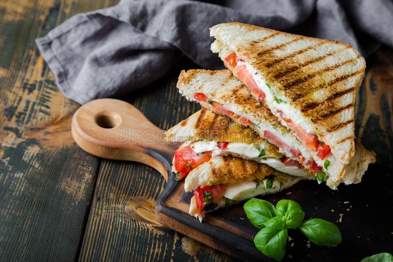 Sandwiches with mozzarella, basil and tomatoes. Italian sandwich. Grilled Italian sausage sandwich with mozzarella and tomatoes royalty free stock photos