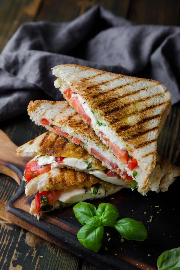 Sandwiches with mozzarella, basil and tomatoes. Italian sandwich. Grilled Italian sausage sandwich with mozzarella and tomatoes stock image