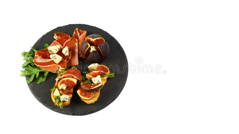 Sandwiches with prosciutto, fresh figs, dorblyu and berries On a shale board is isolated on a white background. top view, copy spa stock photos
