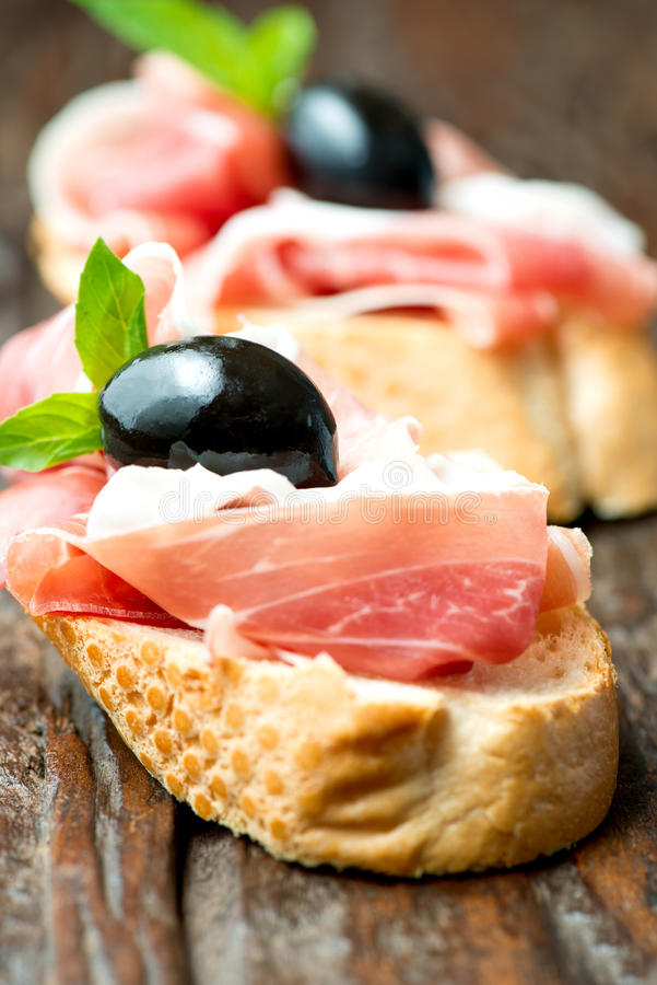 Sandwiches with prosciutto olive on wooden cutting board vertical stock images