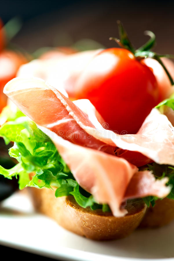 Sandwiches with prosciutto on plate close up stock photo