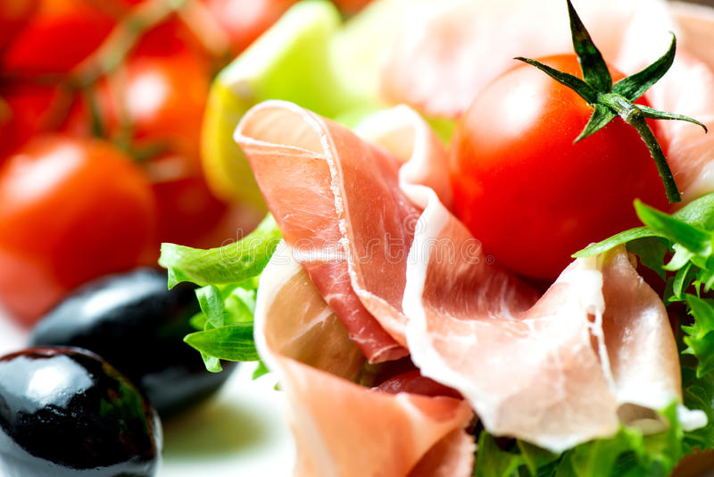 Sandwiches with prosciutto on plate with olive close up stock image