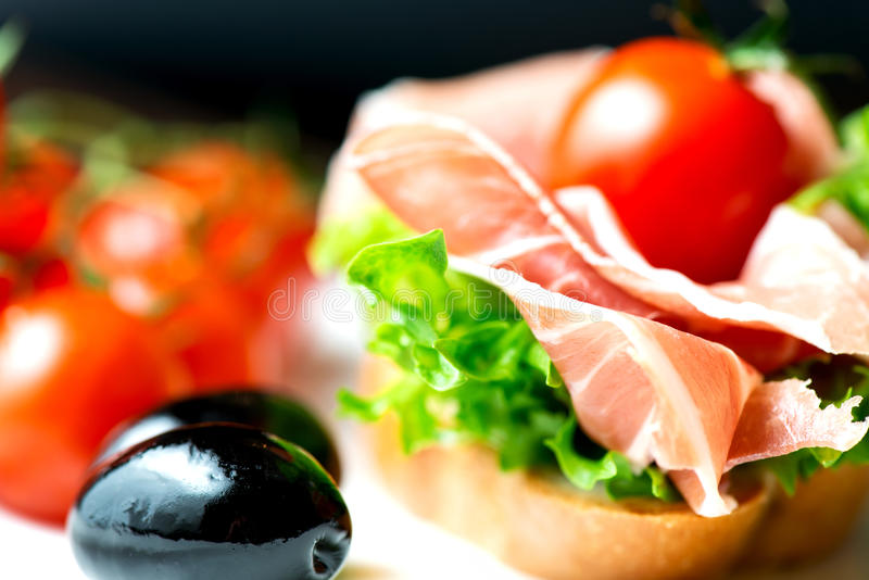 Sandwiches with prosciutto on plate with olive stock photography