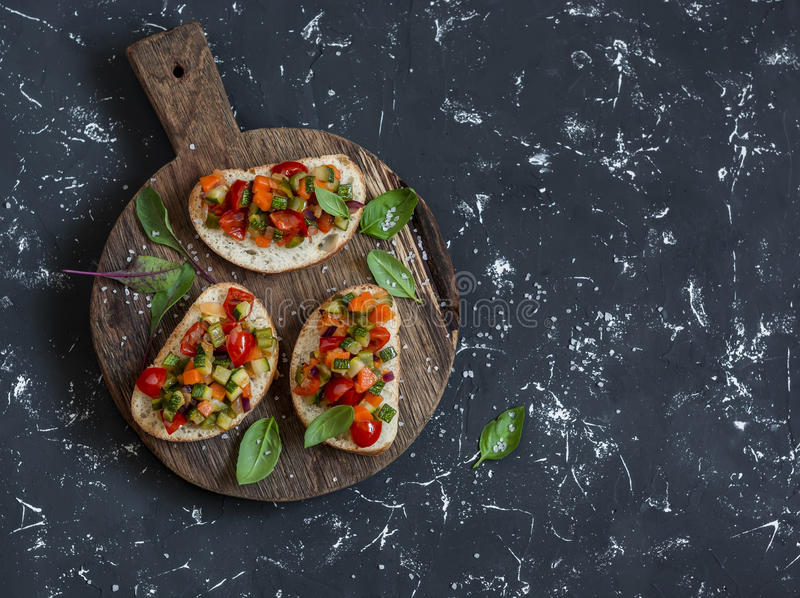 Sandwiches with quick ratatouille on rustic cutting board on a dark background. Delicious healthy vegetarian food. stock images