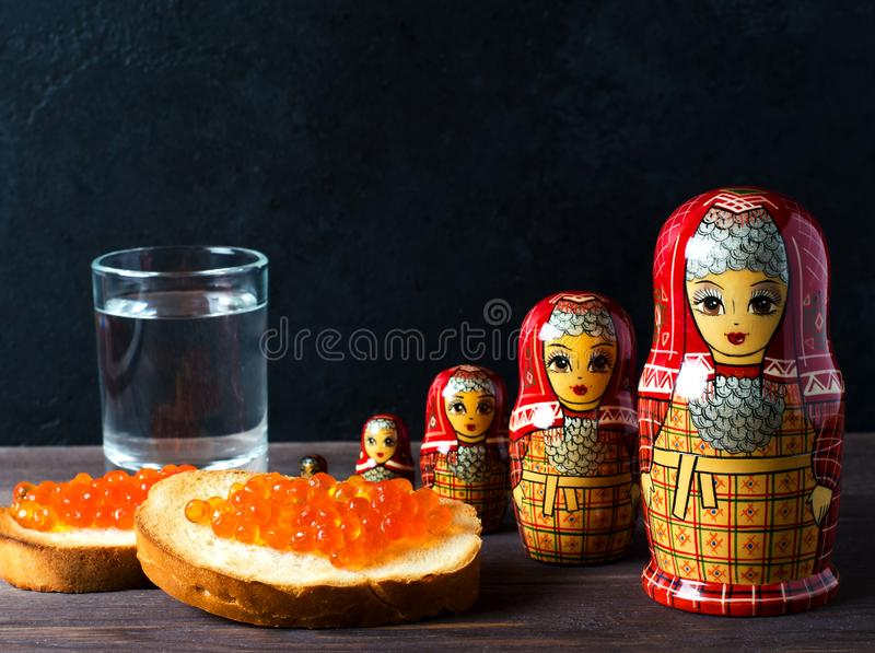 Sandwiches with red caviar of salmon fish. A glass of vodka, matryoshka. The concept of Russian tradition. Copy space.  stock image