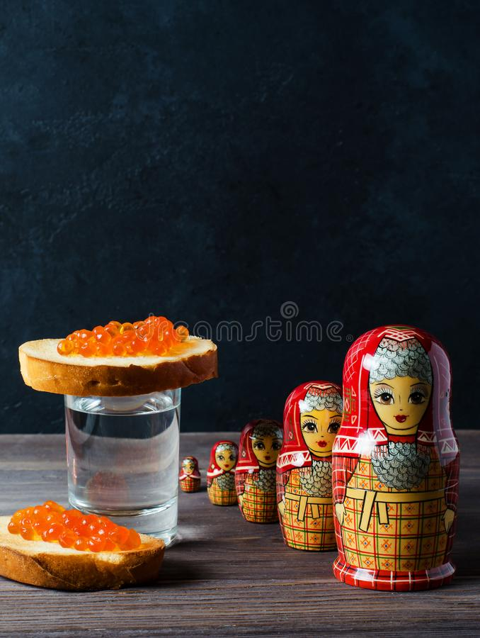 Sandwiches with red caviar of salmon fish. A glass of vodka, matryoshka. The concept of Russian tradition. Copy space. Vertical. Photo royalty free stock photos