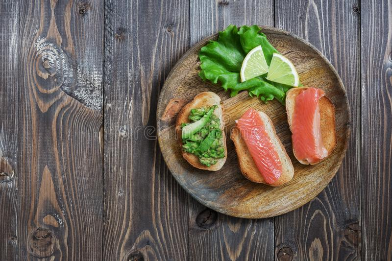 Sandwiches with red fish and avocado, lemon, lettuce, are served on a wooden plate. Top view. royalty free stock image