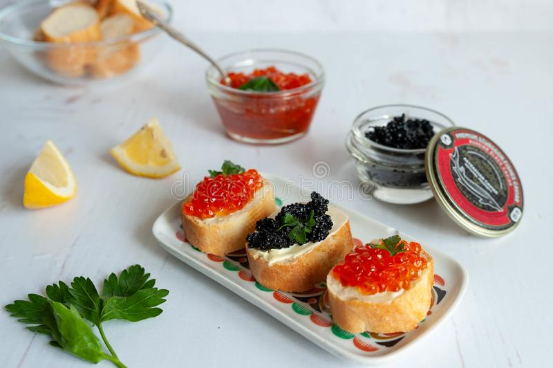 Sandwiches with red salmon caviar and sturgeon black caviar on white background stock images