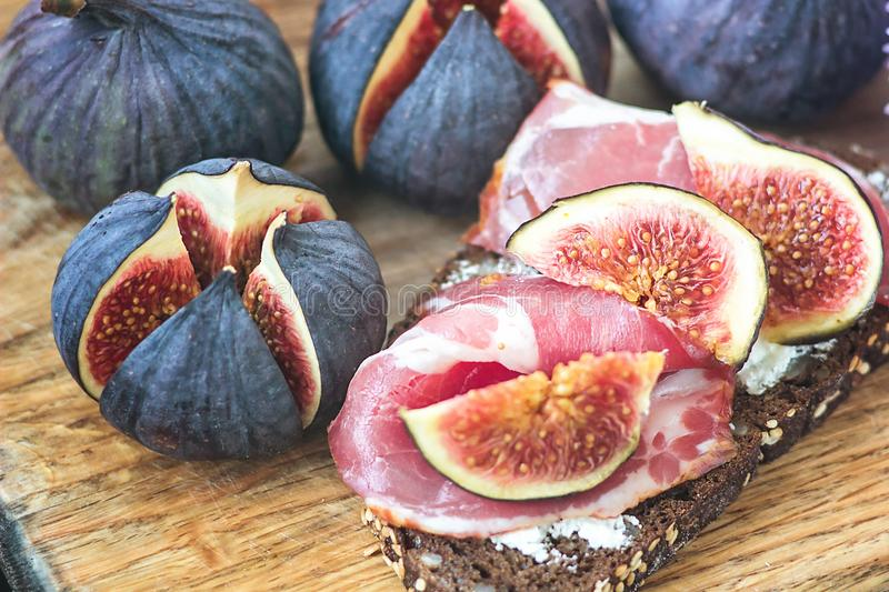 Sandwiches with ricotta cheese, fresh figs and ham, bacon ham prosciutto on rustic wooden cutting board, top view. Delicious tast stock images