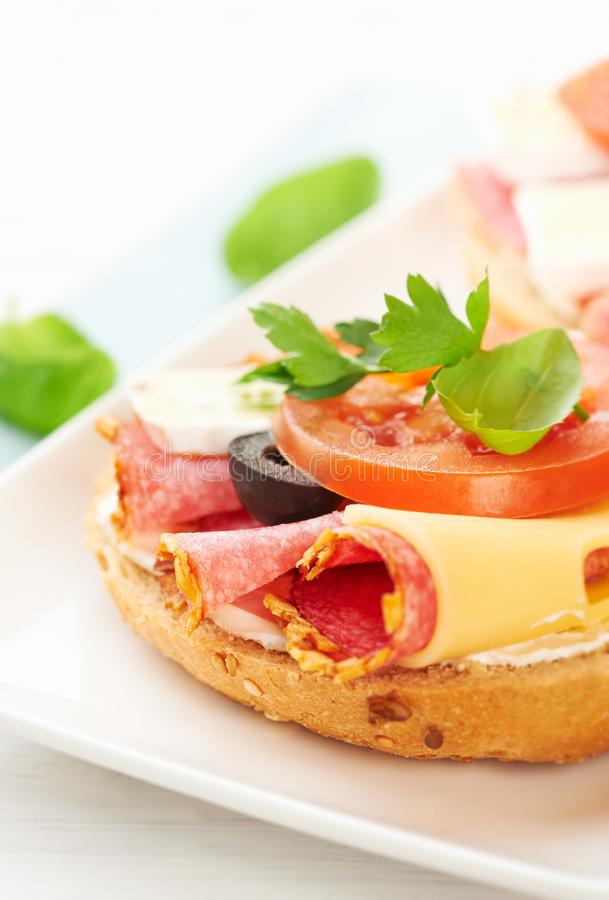Sandwiches with salami, cream cheese, tomatoes, camembert, black olives, fresh parsley and basil served on a plate. royalty free stock photography