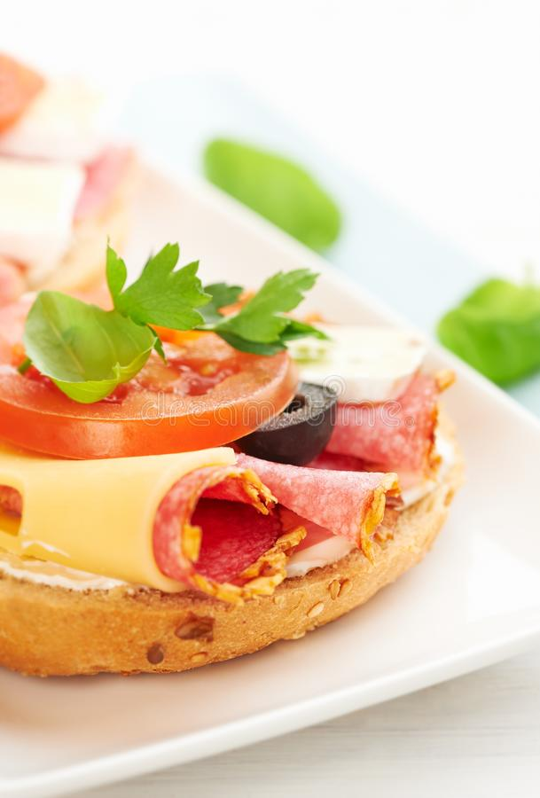 Sandwiches with salami, cream cheese, tomatoes, camembert, black olives, fresh parsley and basil served on a plate. royalty free stock photos