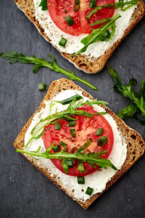 Sandwiches with soft cheese, tomatoes and arugula royalty free stock photography
