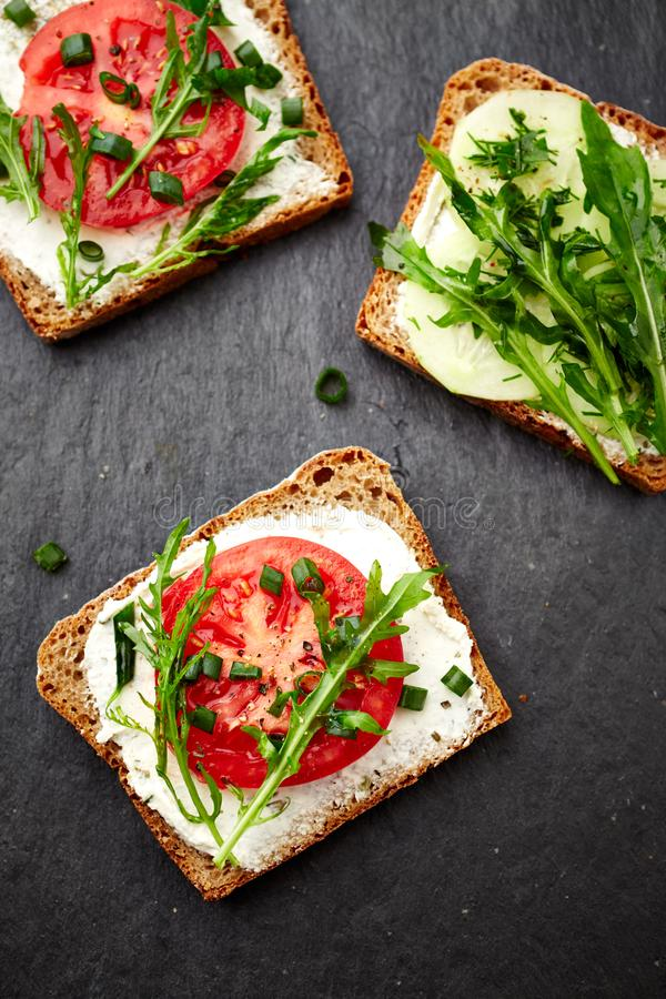 Sandwiches with soft cheese, tomatoes, cucumber and arugula royalty free stock photo