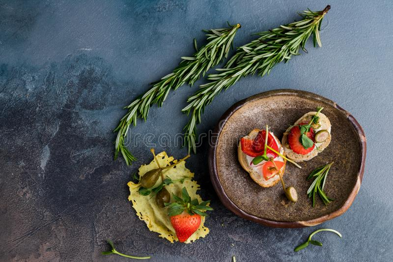 Sandwiches with strawberries, peppers, tomato, radish, lie on a clay plate on a gray concrete background, along with rosemary and. Capers as decoration. free royalty free stock image