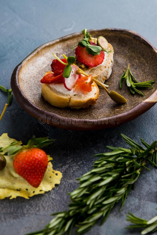 Sandwiches with strawberries, peppers, tomato, radish, lie on a clay plate on a gray concrete background, along with rosemary and. Capers as decoration, close royalty free stock photography