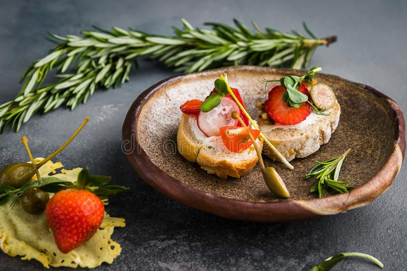 Sandwiches with strawberries, peppers, tomato, radish, lie on a clay plate on a gray concrete background, along with rosemary and. Capers as decoration stock photos