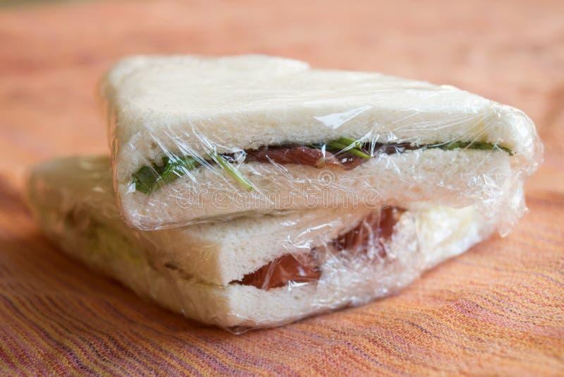 Sandwiches in transparante film worden verpakt die stock foto