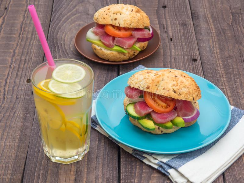 Sandwiches with tuna and vegetables in plates, a glass of lemonade on a table stock image