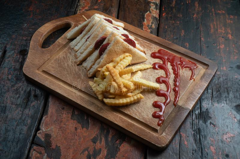 Sandwiches with Turkish sausage sucuk and cheese served aise with french fries on rustic wooden table. Sandwiches with Turkish sausage sucuk and cheese served royalty free stock photography