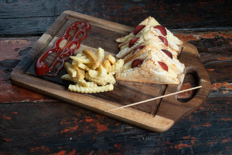 Sandwiches with Turkish sausage sucuk and cheese served aise with french fries on rustic wooden table. Sandwiches with Turkish sausage sucuk and cheese served royalty free stock images