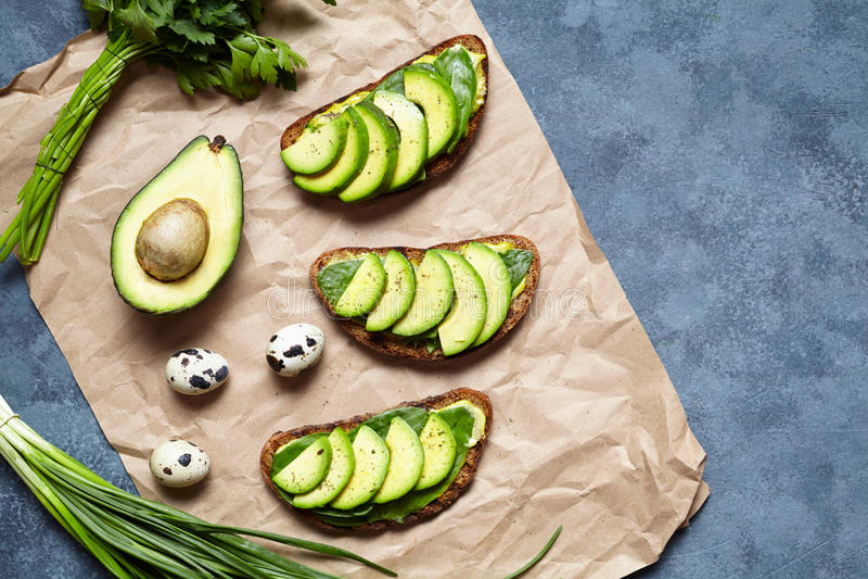 Sandwichestoost met avocado, guacamole en spinazie op perkament op een concrete achtergrond Gezonde ontbijt of lunch royalty-vrije stock foto's