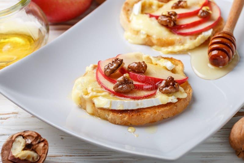 Sandwichs à bruschette avec le brie ou le fromage de camembert, les pommes, les noix et le miel photos libres de droits