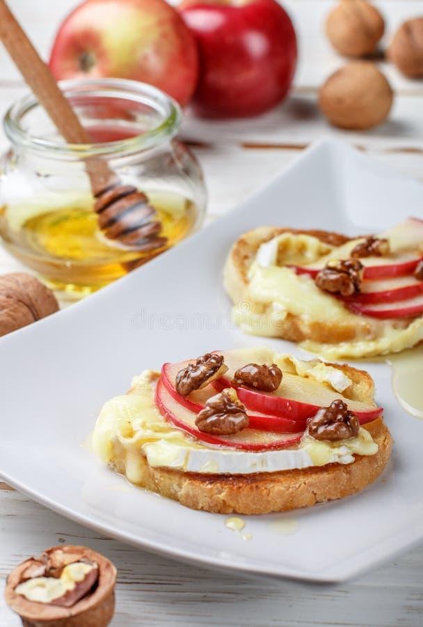 Sandwichs à bruschette avec le brie ou le fromage de camembert, les pommes, les noix et le miel image libre de droits