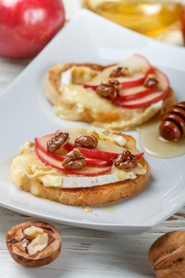 Sandwichs à bruschette avec le brie ou le fromage de camembert, les pommes, les noix et le miel photo libre de droits