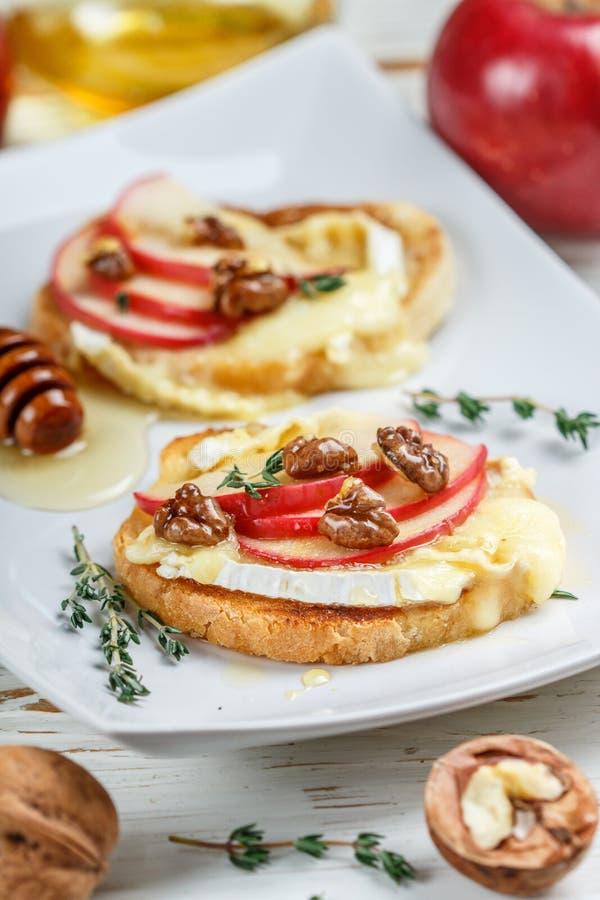 Sandwichs à bruschette avec le brie ou le fromage de camembert, les pommes, les noix, le thym et le miel photos stock