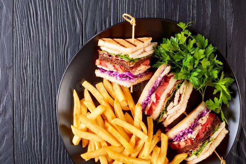 Sandwichs à club posés savoureux avec des pommes frites image libre de droits
