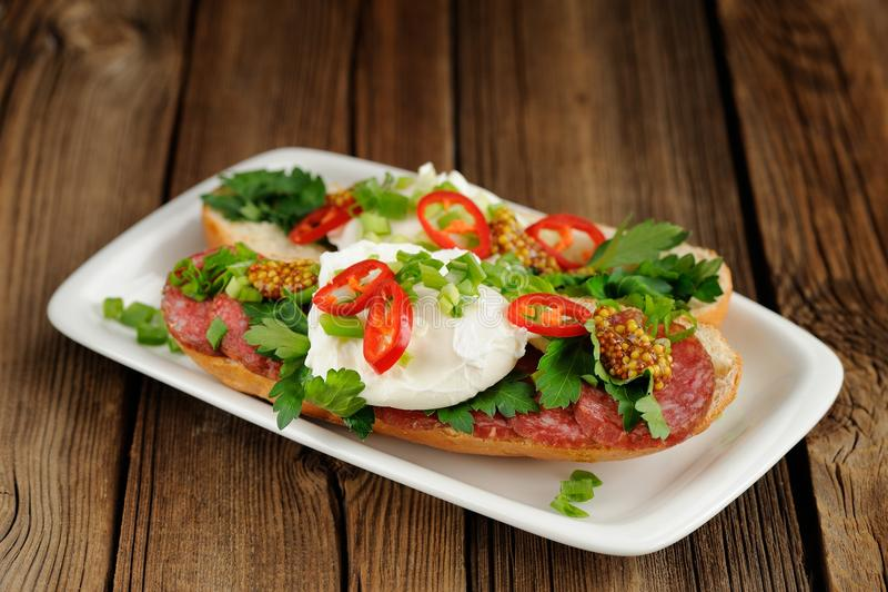 Sandwichs à oeufs pochés avec le piment, l'oignon blanc et le salami photo stock