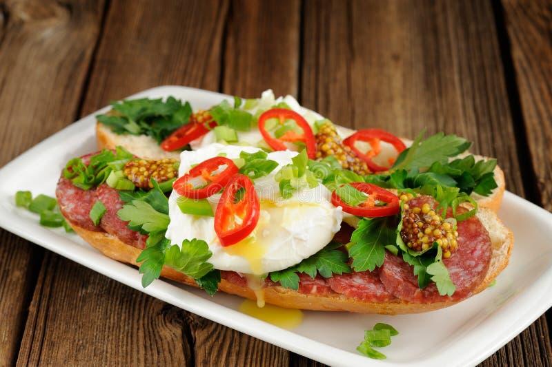 Sandwichs à oeufs pochés avec le piment, l'oignon blanc et le salami images stock