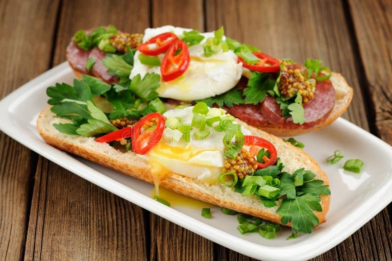 Sandwichs à oeufs pochés avec le piment, l'oignon blanc et le salami images libres de droits