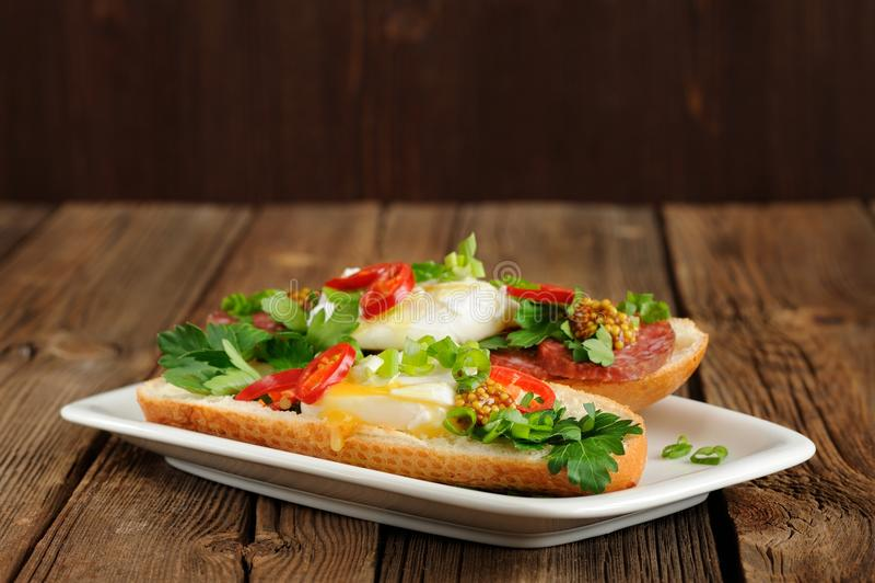 Sandwichs à oeufs pochés avec le piment, l'oignon blanc et le salami image stock